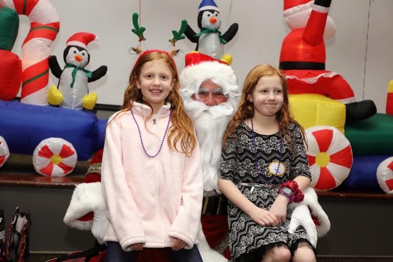 Two girls smiling on Santa's lap