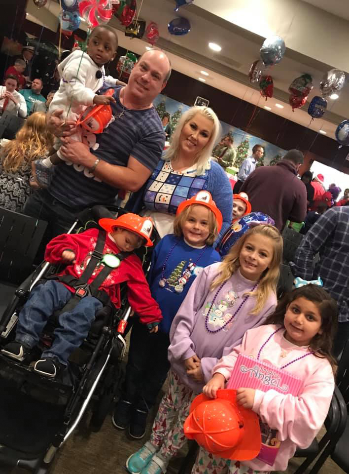 Couple with 5 children with orange plastic firefighter hats