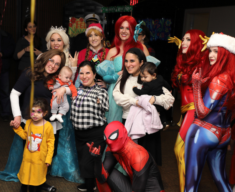 Family of three women and three young children smiling with Disney Princesses and comic book superhero and villainess