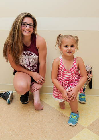 Brooklynn and Danica, two patients who have undergone the rotationplasty procedure, kneeling to show how their feet are used as knee joints.