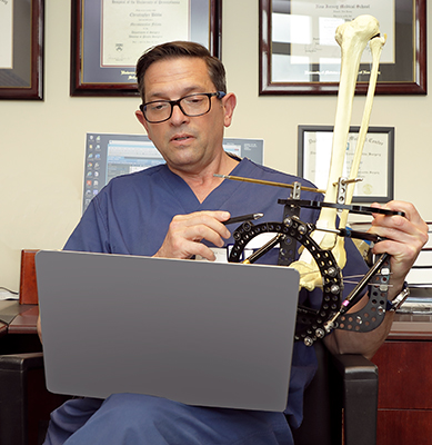 Dr. Christopher Bibbo holding a bone model in an external fixator while talking to a patient on a virtual doctor visit.