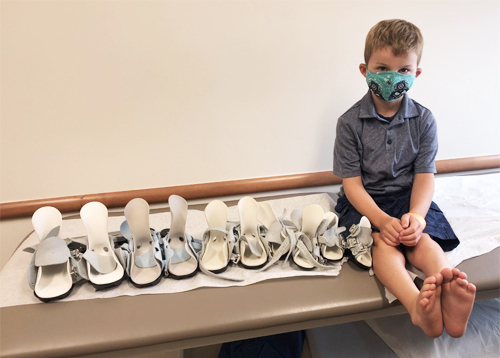Evan sitting with a series of his clubfoot boots that he is donating for other children