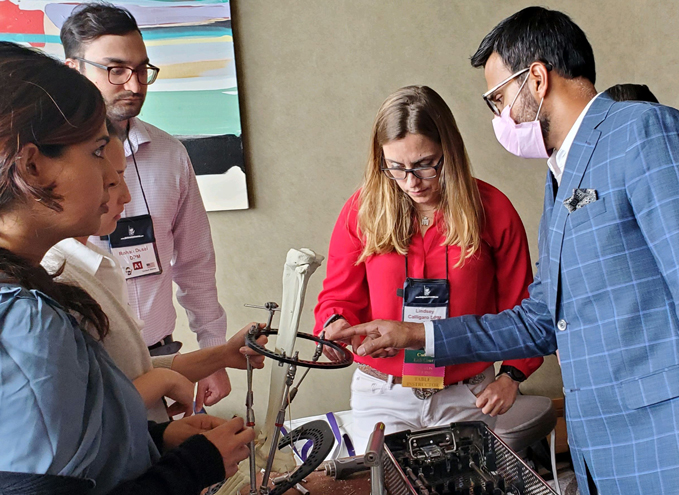 Dr. Noman Siddiqui teaching deformity correction on a sawbone model of a tibia with an external fixator attached to it
