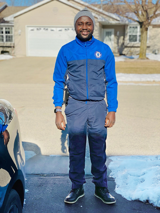 Ebou standing with his feet normally aligned after treatment wearing boots and outdoor gear in the snow