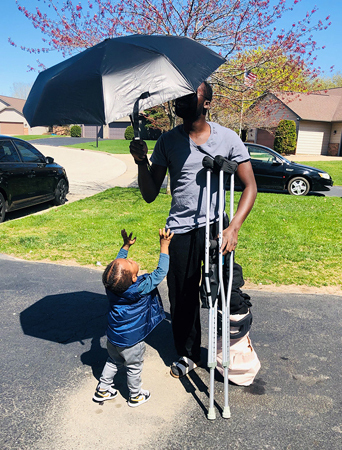 Ebou on crutches while holding an umbrella and walking with his young son