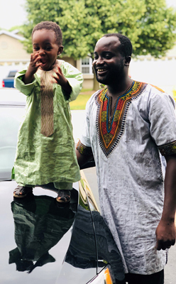 Ebou smiling with his young son on a car