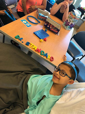JJ spelling out Dr. Standard's name in Play-doh on a hospital table