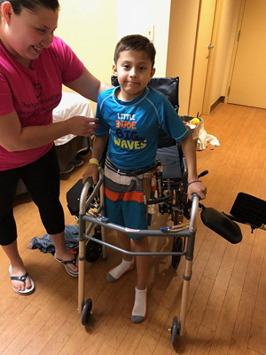JJ wearing his external fixator and using a walker