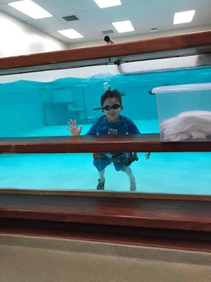 JJ wearing his external fixator doing physical therapy in the pool at the Rubin Institute