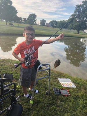 JJ catching a fish while using a walker with his wheelchair in the background