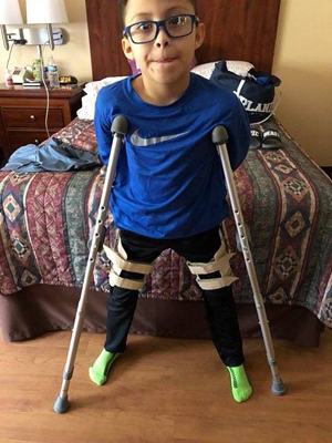 JJ on crutches wearing a brace