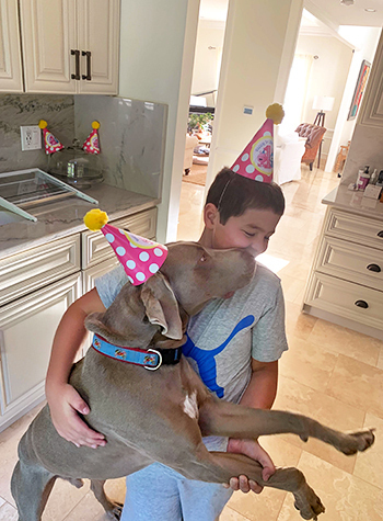 Nicolai and his dog wearing party hats
