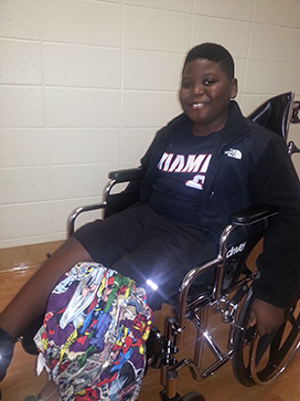Tamarus when he was a younger boy sitting in a wheelchair with a covered external fixator