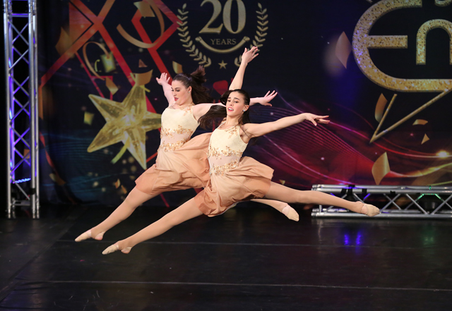 Cassidy and her sister Abby doing split leaps at a dance competition